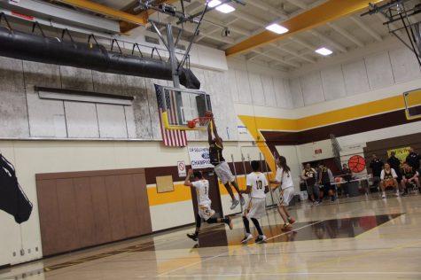Coach Wilson slam dunks the ball into the net.