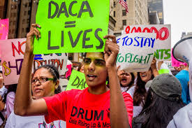 DACA advocates (or 'Dreamers') march in front of Trump Tower, holding signs saying,