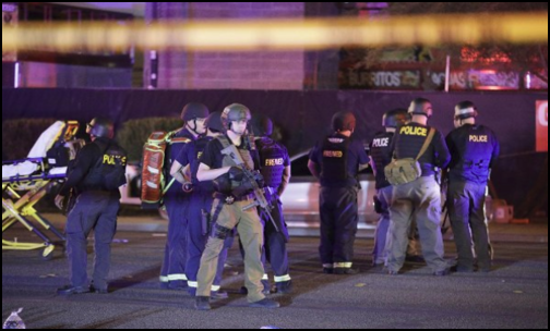 Medical personnel and police officers standing at the scene of a shooting in Mandalay Bay. Photo from Public Domain.