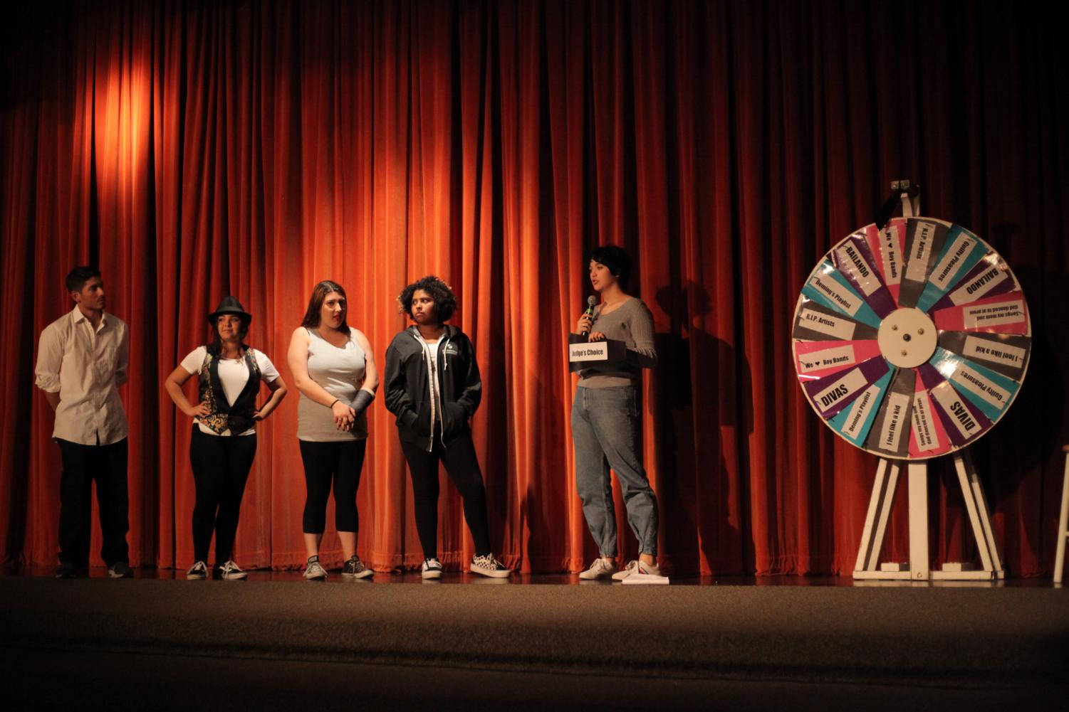 Team leaders (left to right) Jonathan, Dalia, Mikaela, and Olivia stand alongside MC Hailey. The four judges had to spin the wheel to determine what category they will perform.