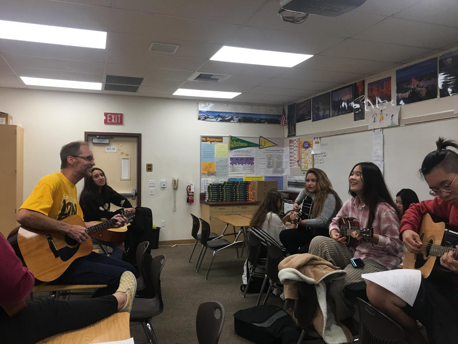 Mr.Robinson's sits in front of students, teaching them the craft of music.