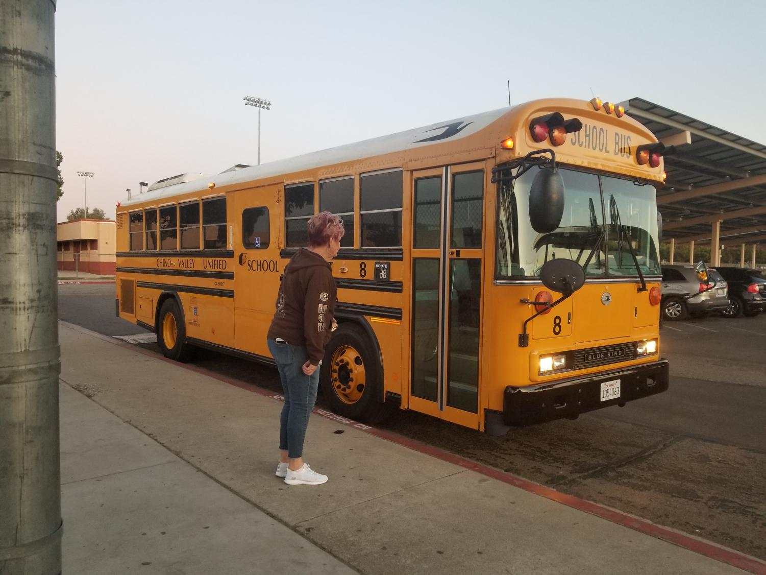Teacher greeting Don Lugo students while they arrive to school and exist the bus early in the morning (Photo Credit Patricia Redaelly)