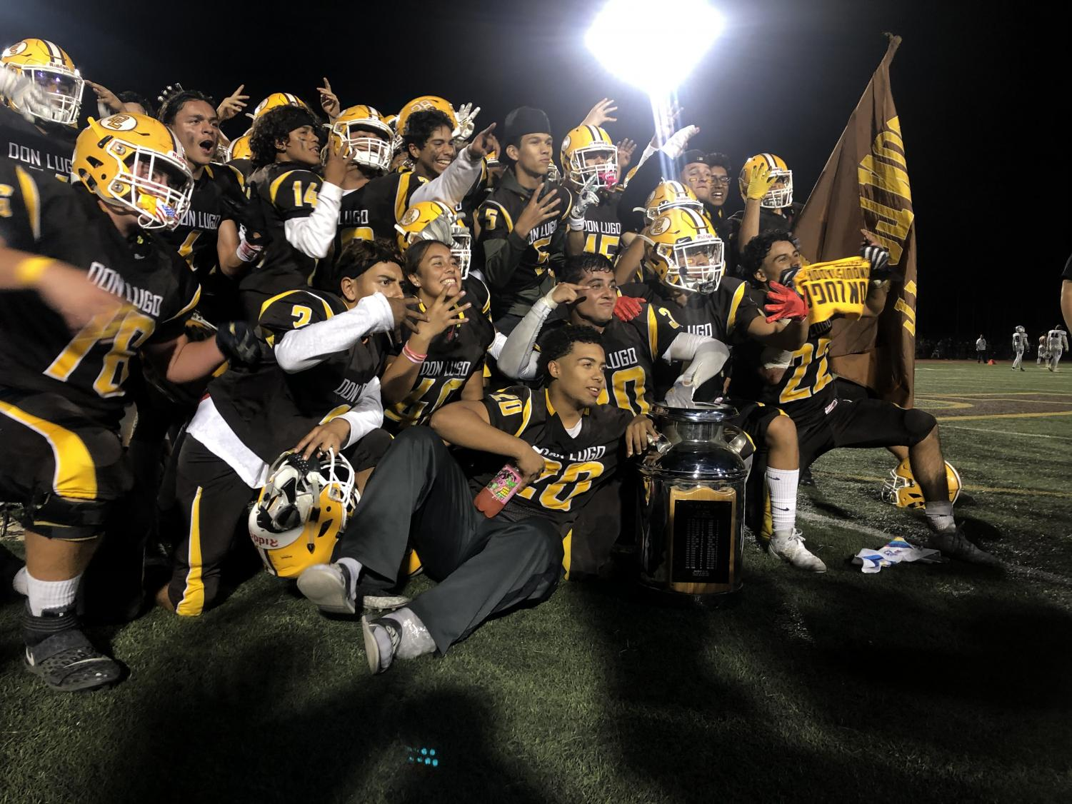 Lugo Football team win 4th straight Milkcan game 15-14. Football Team celebrating win with team picture with Milkcan trophy.