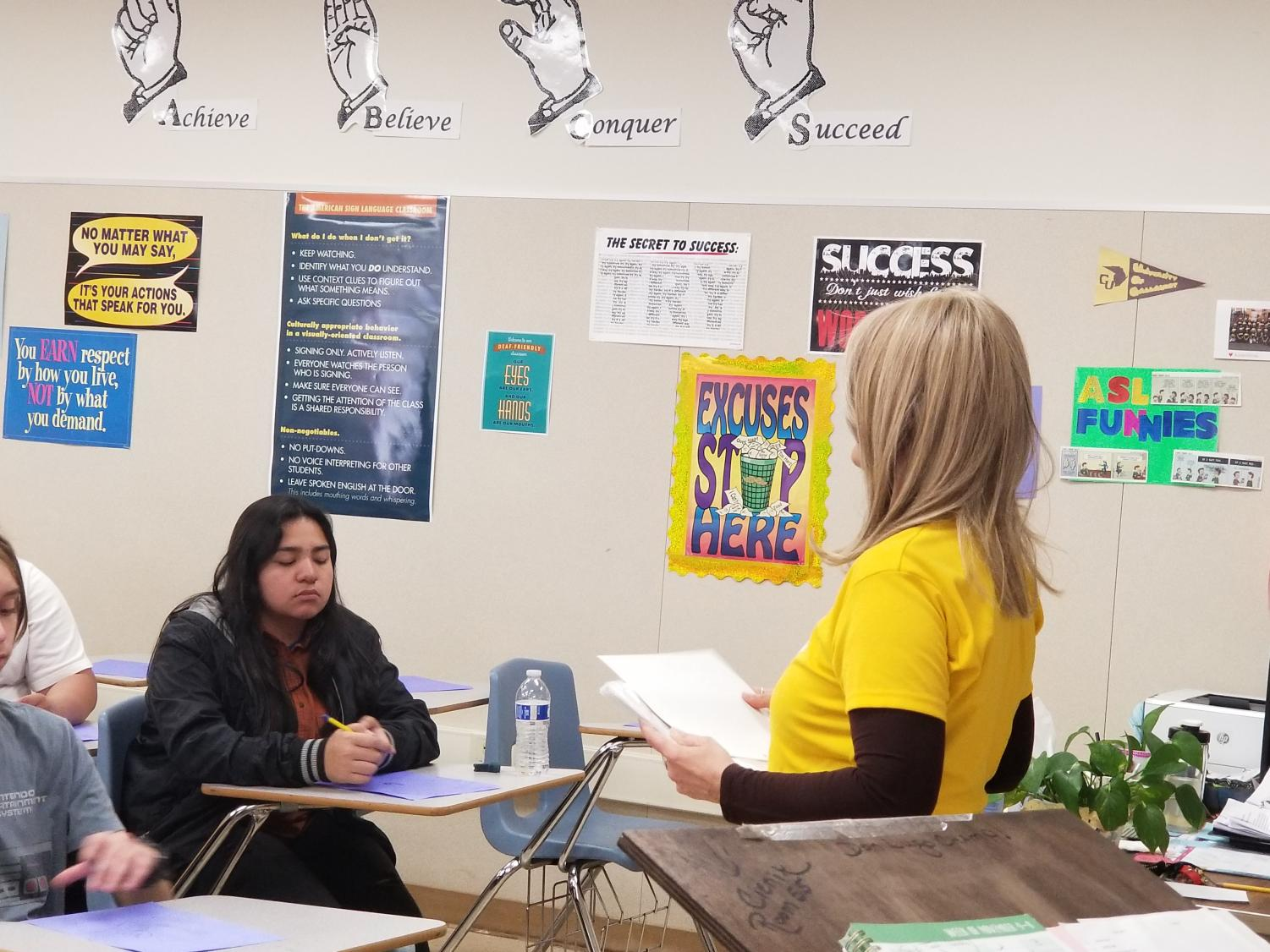 Mrs. Cenik has to constantly stand in the front of the class so that her students can easily see her signs.