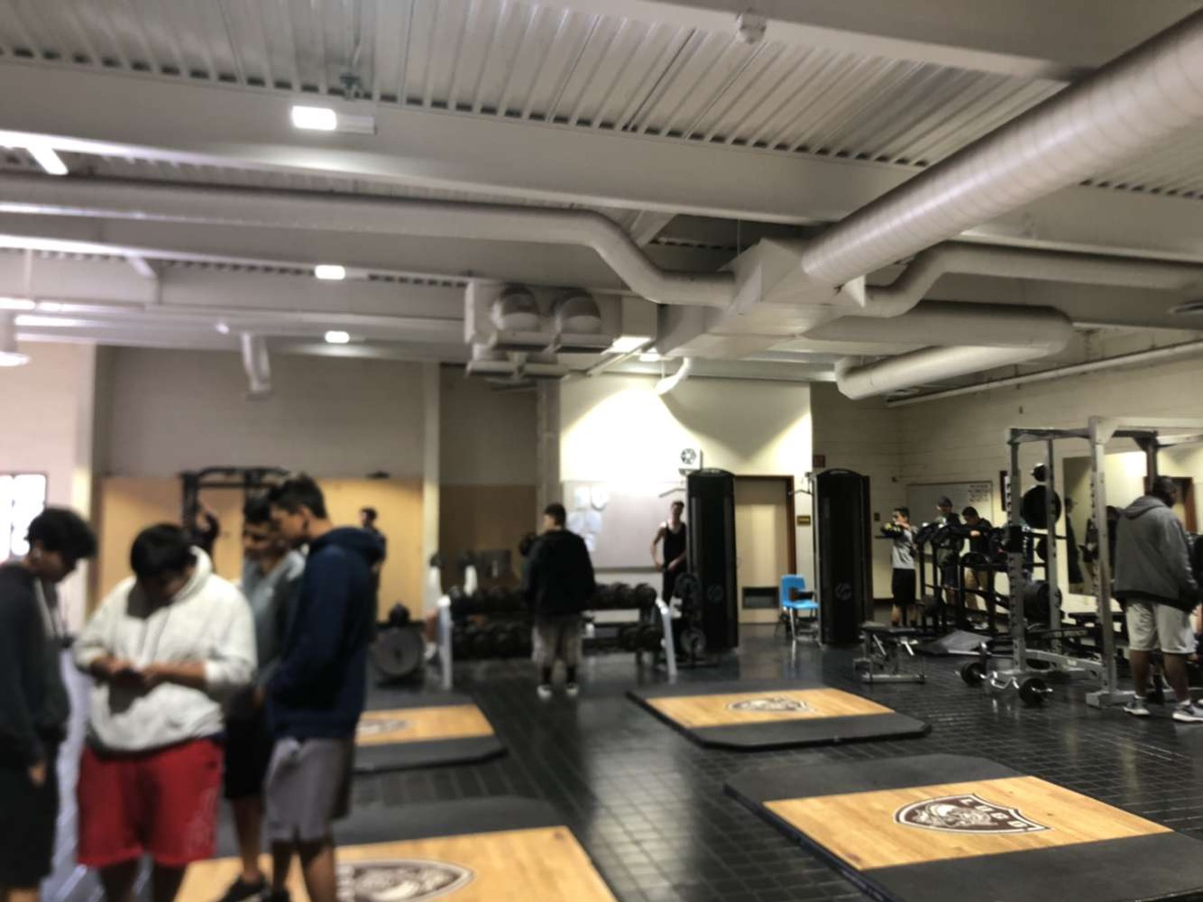 Athletes inside weight room during 4th period. During off-season football athletes make their improvement in the weight room.
