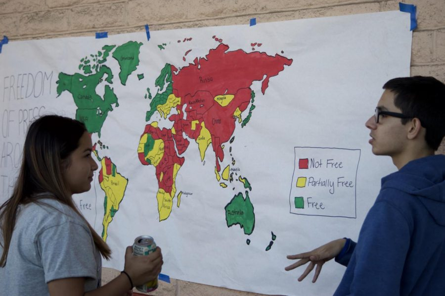 Aiden Deming explaining to classmate and peer, Natalia Reyes the meaning of this red, yellow, and green shaded map. Being the biggest poster in the quad is bound to catch someones eye.