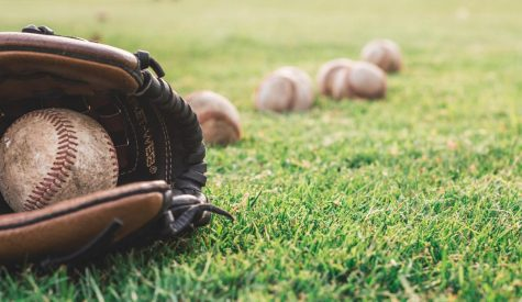 Baseball mitt laying down on grass with baseball inside. (Photo Courtesy: Pexels.com)