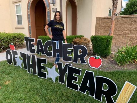 2019-2020 Secondary Teacher of the Year, Mrs. Annette Deming, stands proudly in her Don Lugo staff shirt.