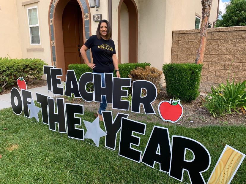 "2019-2020 Secondary Teacher of the Year, Mrs. Annette Deming, stands proudly in her Don Lugo staff shirt. ""I"