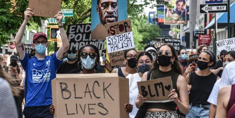 "Protestors holding up ""Black Lives Matter"" signs during protest in New York City."
