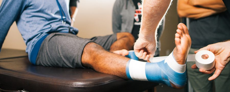 Athletic trainer wrapping athlete's ankle prior to game. (Photo courtesy of SportMedBC.org)