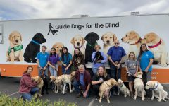 Guide Dogs For the Blind puppy trainers take picture in front of departure truck as the dogs are being sent to training in San Rafael, California. Each puppy will be evaluated within the course of a few months on their effectiveness of being a guide dog and take on tasks in real-life situations that people who are blind will encounter.