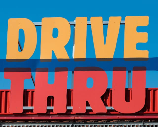 Drive-Thru Logo symbolizing there is a drive-thru nearby. Often Drive-Thru logos are a sign of fast food restaurants to get your food in a hurry and effectively, however with new guidelines regarding COVID more and more companies other than the food industry are taking part in creating a drive-thru method for consumers to get their desired items while staying safe with CDC guidelines.