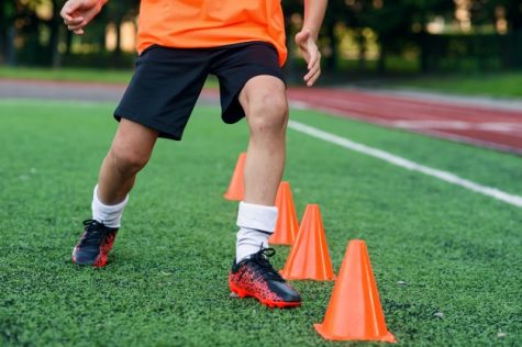 Close-up shot of soccer player dribbling through cones. (Photo courtesy of Pixabay.com)