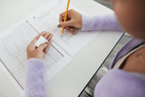 A student is using a small paper of notes to cheat on an exam. (Photo curtesy: Pexels.com)