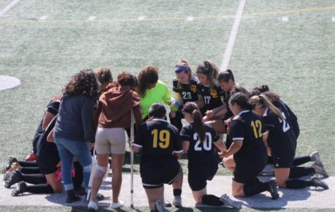 The girls soccer team from the 2020-2021 season huddled on the field before the start of their soccer game.