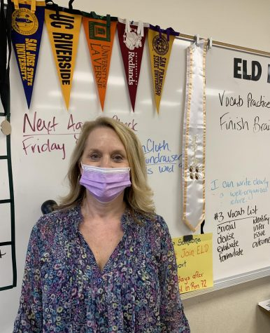 Mrs. Dominguez standing in front of the college banners present in her classroom. Avid teachers promote to Avid students going to a 4-year university.