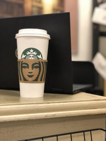 A Starbucks coffee cup sits on a desk with a laptop directly behind it.
