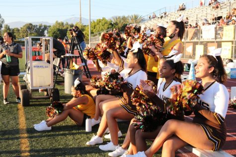 """The Don Lugo Cheerleaders are showing their support for our football team by chanting and waving their pom-poms in the air. """""""