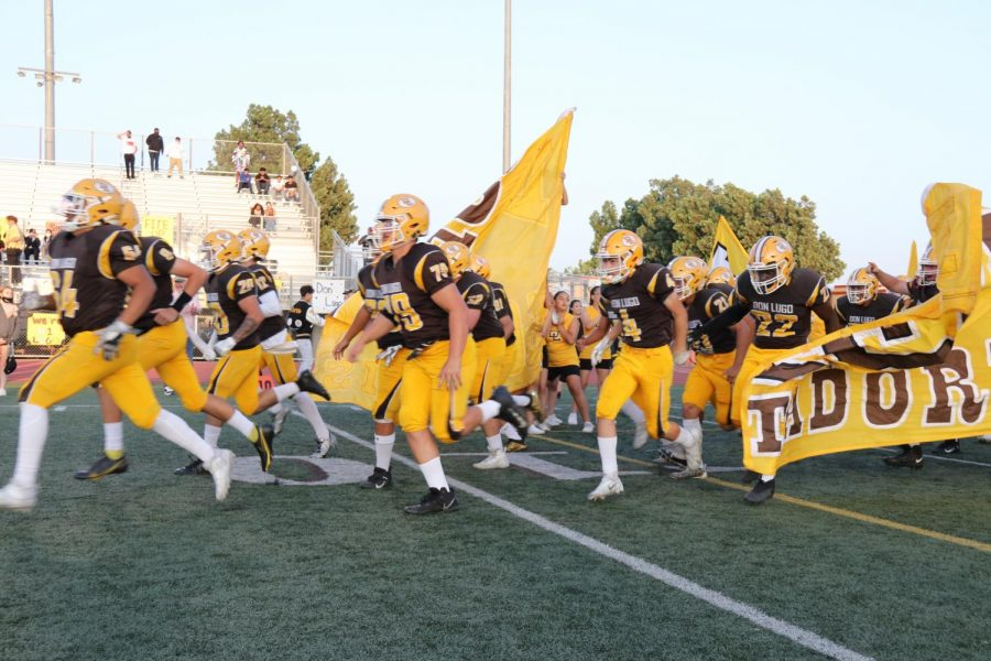 Don Lugos varsity football team is running out of the tunnel at a game.